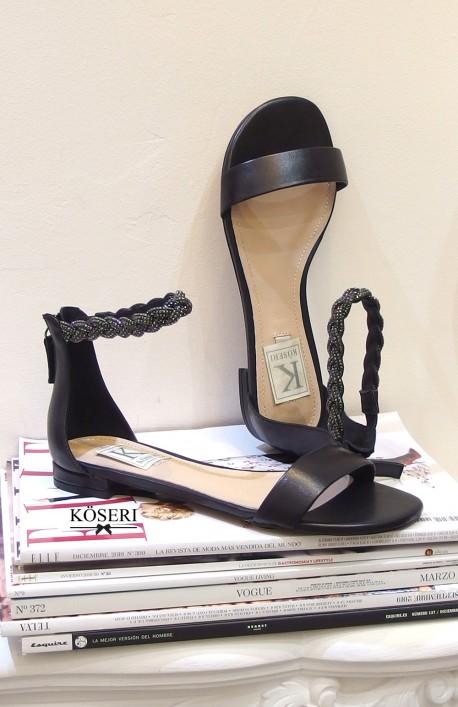 Sandalia plana negra con pulsera de cristales.